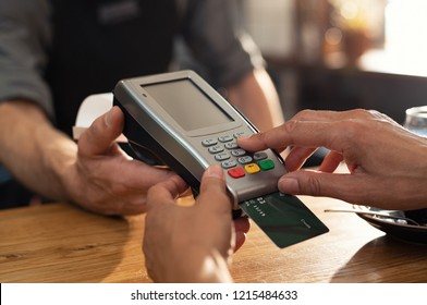 Closeup of hand using credit card swiping machine to pay. Female hand with credit card paying through terminal for payment in coffee shop. Woman entering debit card code in swipe machine.