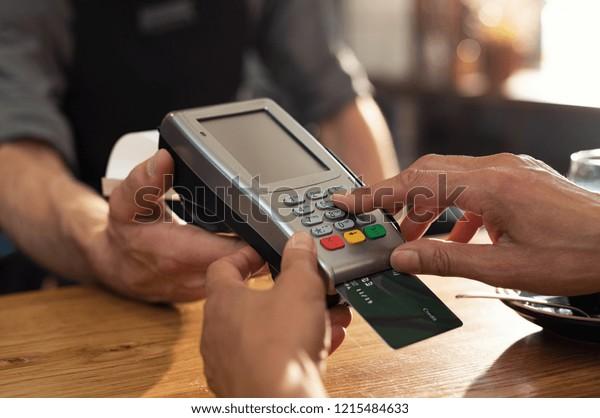 クレジットカードのスワイプ機を使用した手の接写で支払う。喫茶店での支払いのためにターミナルで支払うクレジットカードを持つ女性の手。スワイプマシンでデビットカードコードを入力する女性。