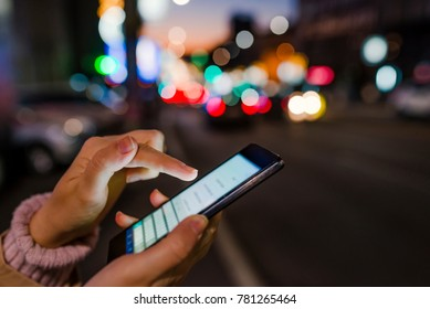 Close-up hand using phone in night time on street. Woman Using Smartphone on European Christmas Market. Girl pointing finger on screen smart phone on background illumination color light in night city