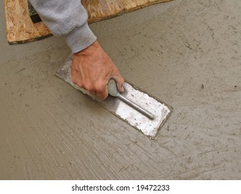 Close-up of hand using trowel to finish concrete slab
