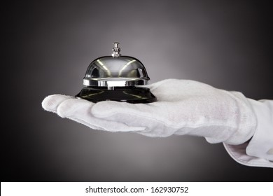 Close-up Of Hand With White Gloves Holding Service Bell