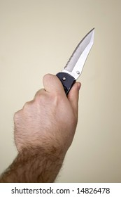 Closeup of a hand wielding a knife with a very sharp blade.