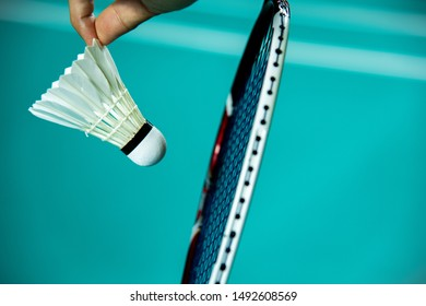 Closeup hand of woman Badminton player holding shuttlecock and racket ready to SERVE with green blur Badminton court background.