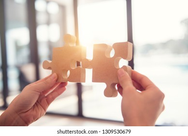 Closeup hand of woman connecting jigsaw puzzle with sunlight effect, Business solutions, success and strategy concept.