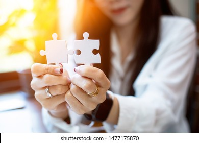 Closeup hand of woman connecting jigsaw puzzle,Business solutions, success and strategy concept