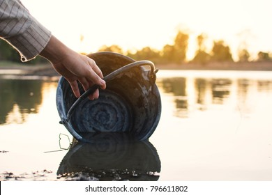 Close-up hand of woman holding a bucket on lake, crisis of water and drought