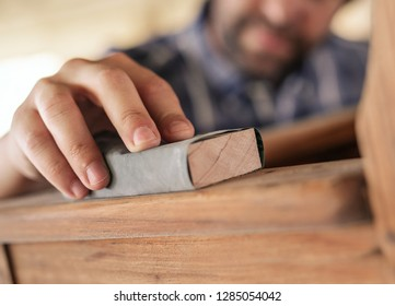Closeup of hand of woodworker using sandpaper to sand a wooden chair while working in his woodworking shop