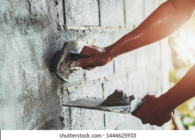 closeup hand of worker plastering cement at wall for building house