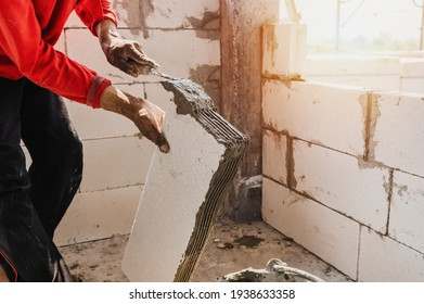 closeup hand of worker plastering cement on brick for building house