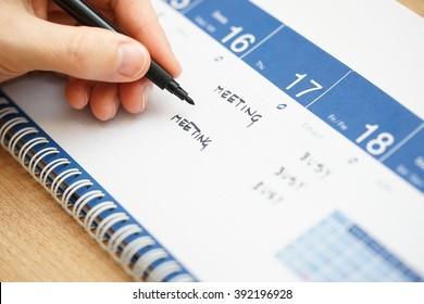closeup of hand writing events on calendar