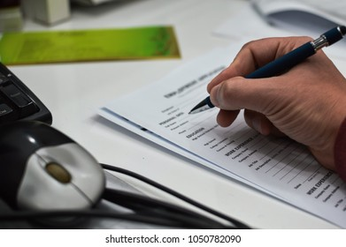 Closeup of hand writing filling job or service application form over light desk background. Signing with pen checklist, college student or education university program certificate. Business contract