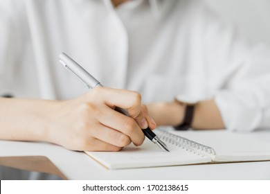 Close-up of hand writing on blank notebook on table in house.