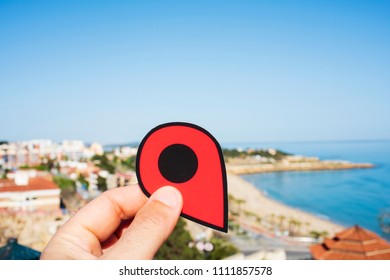 closeup of the hand of a young caucasian man with a red marker pointing the Miracle Beach in Tarragona, Spain, the main beach of the city