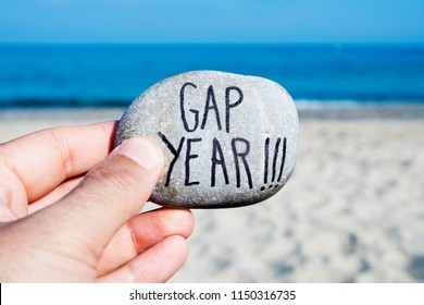 closeup of the hand of a young caucasian man on the beach, in front of the ocean, holding a stone with the text gap year written in it