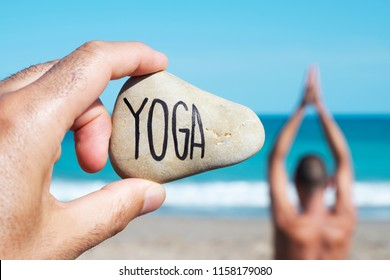 closeup of the hand of a young caucasian man on the beach holding a stone with the yoga written in it, and a young caucasian man practicing yoga in the background
