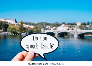 closeup of the hand of a young caucasian man showing a speech bubble with the question do you speak Czech written in it, next to the Vltava river in Prague, Czech Republic