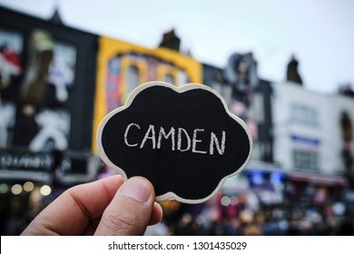 closeup of the hand of a young caucasian man holding a black signboard with the word Camden written in it, in Camden High Street, in the popular Camden Town district in London, United Kingdom
