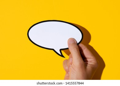 closeup of the hand of a young caucasian man holding a blank speech balloon against a yellow background, with a hard shadow