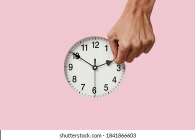 closeup of the hand of a young caucasian man setting a clock backward or forward, at the end or at the beginning of the summer, on a pink background