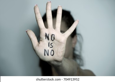 closeup of the hand of a young caucasian woman in front of her face with the text no is no written in her palm