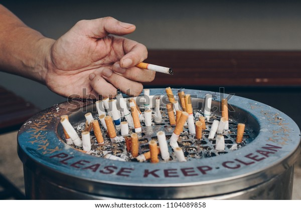 Close-up of the hand of young man with group of Cigarettes left in the metal ashtray. Public smoking area.