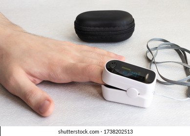 Close-up of the hand of a young man measuring the level of oxygen saturation of the blood with a pulse oximeter.Modern technologies for health protection