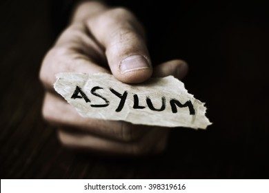 closeup of the hand of a young man with a piece of paper with the word asylum, with a dramatic effect
