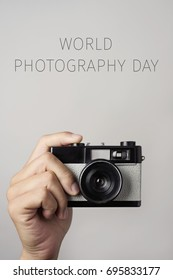 closeup of the hand of a young man with a retro film camera and the text world photography day against an off-white background