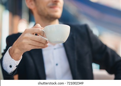 Close-up hand of young smiling businessman in formal wear holding cup, mug of coffee