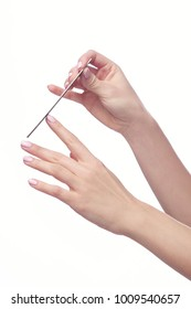 A closeup of the hand of a young woman filing nails, on a white background.