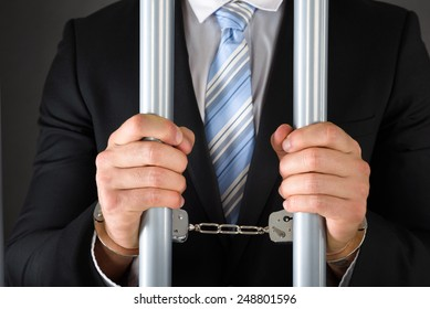 Close-up Of Handcuffed Businessman In Jail Holding Metal Bars