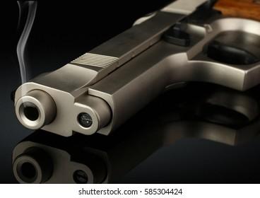 Closeup of handgun with smoke barrel on black, soft focus