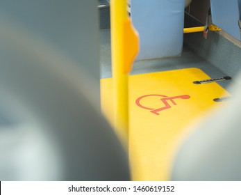 Close-up handicap logo in a bus. Priority seat for disabled people. Wheelchair accessible transportation concept.