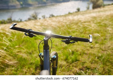 Close-up of the handlaber of mountain bicycle against beautiful landscape in summer season.