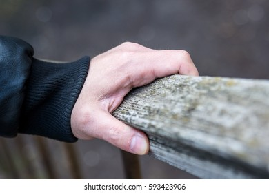 Close-up of handrail and the man's hand
