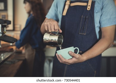 closeup hands asian man barista making coffee in coffeshop