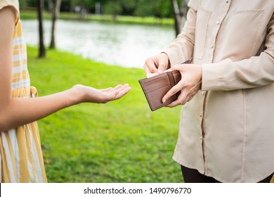 Closeup hands of asian woman hands open wallet,mother or guardian giving pocket money to daughter in green nature,child girl demanding money,allowance,parent pulls out money from wallet to give her