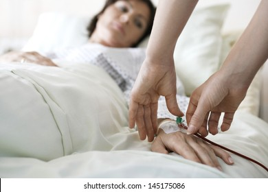 Closeup of hands attaching intravenous tube to patient's hand in hospital bed