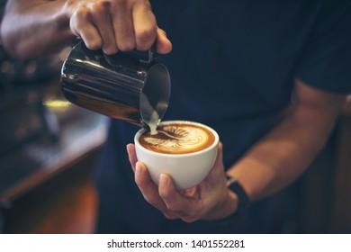 Close-up of hands barista make latte coffee art paint