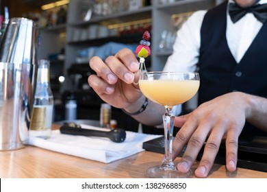 Close-Up of the Hands of a Black African American Waiter Serving Cocktails Glass