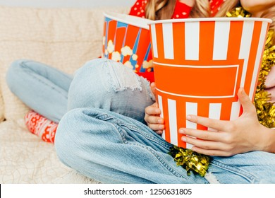Close-up, in the hands of a bucket of popcorn, watching a movie at home. Cinema