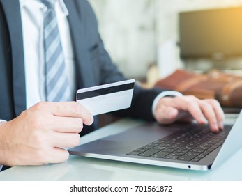 Close-up of hands businessman shopping and paying online using laptop and credit card