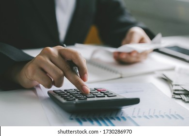 Closeup hands of businessman working on desk office with using a calculator to calculate the numbers, finance accounting concept