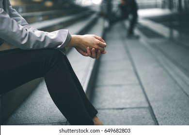 Close-up hands of businesswoman stressed from work while sitting outdoors on the stairs, concept work life balance, burn out syndrome, press from colleagues.