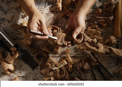 Closeup of hands carving wood.