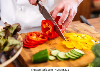 Closeup of hands of chef cook cutting vegetables on wooden table