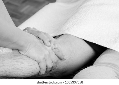 Closeup of hands of chiropractor, physiotherapist doing calf muscle massage to man patient. Osteopathy.