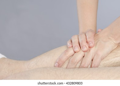Closeup of hands of chiropractor / physiotherapist doing calf muscle massage to man patient.