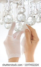 closeup of hands cleaning the chandelier with serviette