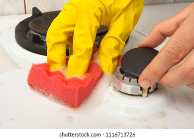closeup of hands cleaning gas cooker in the kitchen